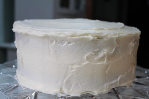 "Frost the cake with Cream Cheese Frosting. If it starts getting crumbs in the frosting, give it a light  ""base coat,"" freeze, then give it a nice thick covering with the frosting."