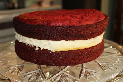 I got so busy putting the cake together, I skipped a few shots. Basically, let your cake cool, take your frozen cheesecake out of the freezer. Frost both the two sides of cake layers that will connect with the cheesecake and put them together.
