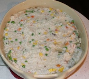 Layer pre-cooked chicken into a casserole pan (sprayed with non-stick spray - the pan, not the chicken). I cut the chicken into bite-size pieces before layering in the pan. Top with veggie and rice mixture then cover in foil.