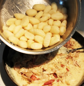 Add cooked gnocchi and stir to coat, then spoon into a greased baking dish.