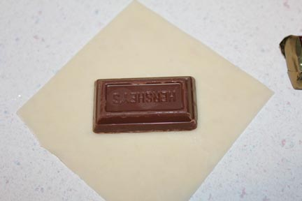 Place a miniature chocolate candy bar in the center of a Won Ton wrap.